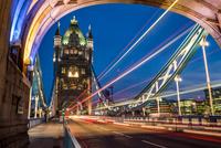 Traffic light trails on Tower Bridge at night, London, England, UK