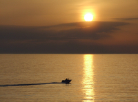 Silhouette of boat on ocean at sunset