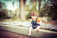 Baby boy (6-11 months) sitting in park