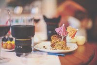 Table with glass of wine, lens and cake with two umbrellas