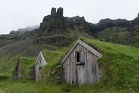Wooden huts covered with green grass beneath rocky mountain peak, Iceland