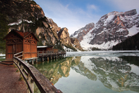 Hut and pier on Lake Braies shore under mountains of Dolomites, Bolzano, South Tyrol, Italy