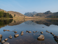 Rocks in Blea Tarn lake surrounded by mountains under clear sky in moorlands of Lake District, Cumbria, England, UK