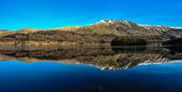 Mountains reflected in calm lake, Lake District, UK