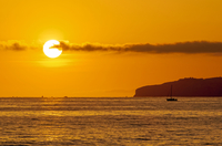 Lone sailboat on sea at orange color sunset, San Clemente, California, USA