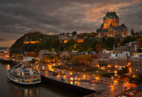 Ferry on Quebec City waterfront under cloudy sky with Fairmont Le Chateau Frontenac visible, Quebec, Canada