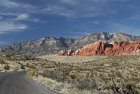 Road, rock formation and mountain range in desolate desert of Red Rock Canyon, Las Vegas, Nevada, USA