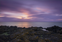 Sunset over North Sea, rocky coast in foreground, EastLothian, Scotland, UK