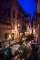 Gondolas on Venetian canal during dusk, Venice, Italy