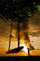 Silhouette of swing and person walking alone at sunset