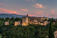 Medieval palace and fortress of Alhambra surrounded by forest at sunset, Granada, Andalusia, Spain