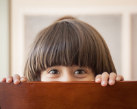 Boy with fringe hair (8-9) peeking behind chair backrest, Pakistan