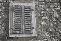 Weathered closed shutters on window in stone wall, Vrsar, Istria, Croatia