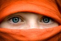 Close up of girl's (8-9) eyes wearing orange burka