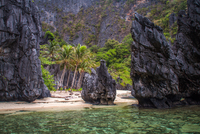 Large rocks on sandy beach, palm trees and cliff in foreground, El Nido, Palawan, Philippines