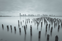 Seascape with wooden piles and remote city skyline, New Jersey, USA