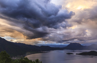 Clouds over Lugu Lake with mountains on shore, Sichuan, China