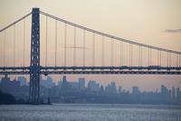 Suspension bridge and Manhattan skyline silhouette, New York City, New York, USA
