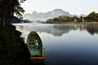 Old boat moored at lakeshore against mountains, Vang Vieng, Vientiane, Laos