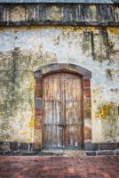Wooden door in weathered wall, Panama City, Panama