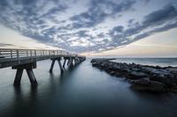 Pier and breakwater on North Atlantic Ocean under cloudy sky, Cape Canaveral, Florida, USA