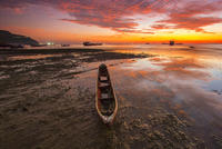 Boats on sea during low tide at sunset, Indonesia