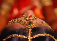 Golden crown decoration with gemstones on women's head, India