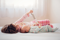 Two sisters (2-3, 2-5 months) lying on bed and playing with digital tablet