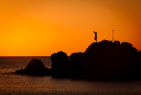 Silhouette of man raising hands on rock, Hawaii, USA