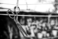 Rusty scissors hanging on clothes line against blurry background