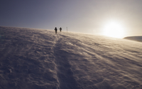 Silhouette of two hikers on snowy mountain, Bulgaria
