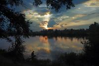 Man fishing on lake at sunset