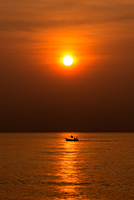 Lone boat on Gulf of Thailand at orange color sunset, Thailand