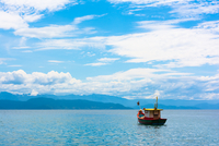 Colorful boat on calm sea under cloudy sky, Ilhabela, Southeast Region, Brazil