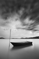 Boat moored to pole on calm lake under moody sky