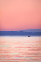 Distant view of single boat on lake at dusk
