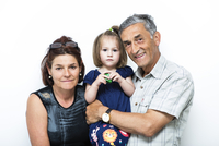 Studio shot of grandparents with granddaughter (2-3)