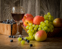 Still life with summer fruits and glass of red wine