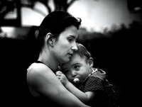 Portrait of mother hugging crying baby (6-11 months)
