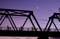 Silhouette of people cycling on bridge against violet sky