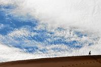 Silhouette of person walking through desert, Sossusvlei, Namibia