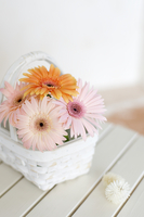 Basket arrangement with gerbera flowers on wooden table