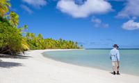 Senior man on sandy beach and Pacific Ocean, Aitutaki, Cook Islands
