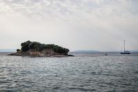 Little island and sailboat on sea, Croatia