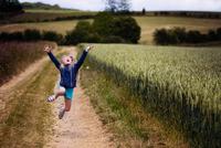 Happy girl (8-9) jumping near wheat field