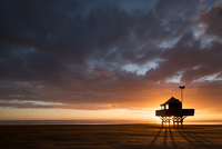 Silhouette of lifeguard hut at sunset, Bethells Beach, North Island, New Zealand