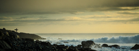Silhouette of surfer on rocks over sea