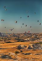 Hot air balloons over rocky mountains, Cappadocia, Central Anatolia, Turkey