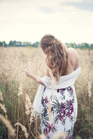 Blonde young woman wearing dress in field