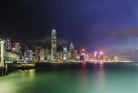 Illuminated cityscape by sea at night, Victoria Harbor, Hong Kong